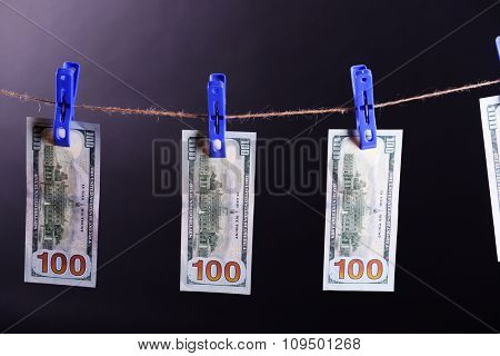 Concept of money laundering - one hundred bills hanging on a cord against grey background