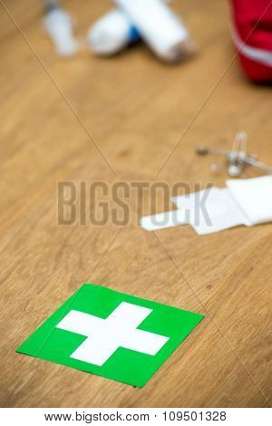First aid kit, indicated by a white cross on a green field on a wooden surface with copy space