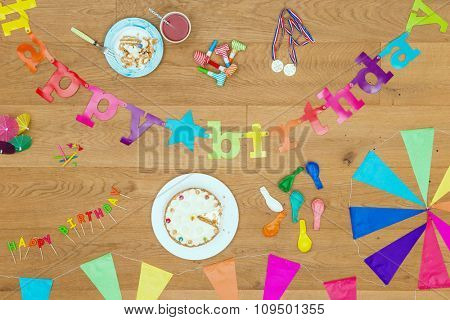 Wooden surface with an assorted array of birthday party items and objects, such as cake, candles, garlands, whistles, balloons and such, seen from above. A top view background for invitations