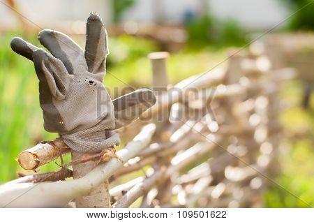 An Old Worn Gardener's Working Glove In A Wicker Fence