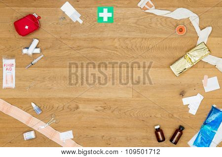 An array of assorted first aid kit objects, including plaster, bandages, desinfectant, scissors, pliers, and such, on a wooden surface, with a lot of copy space in de middle of the image