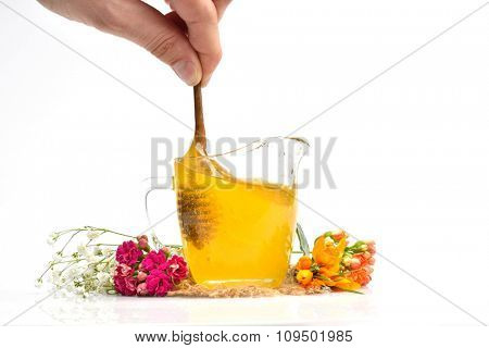 golden honey with wooden stick and flowers isolated on white background