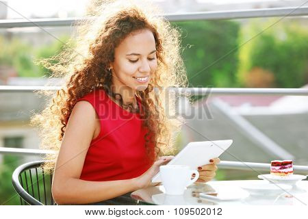 Beautiful young woman with tablet sitting at the terrace
