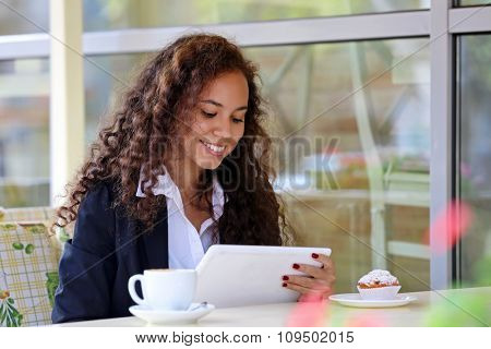 Beautiful business woman with white tablet in the restaurant