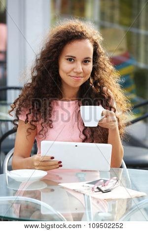 Beautiful young lady with tablet sitting at the summer terrace and drinking coffee