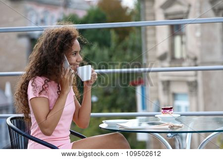 Pretty young woman speaking by cellphone and drinking coffee at summer terrace