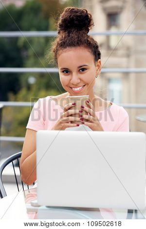Young pretty business woman in red dress with laptop at summer terrace