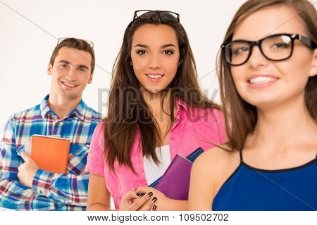 Cheerful Young Students Holding Books And Materials