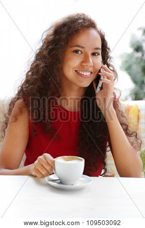 Young smiling woman in red dress speaking by cellphone and drinking coffee at restaurant's terrace