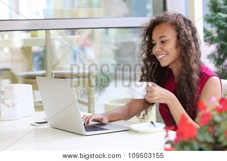 Young pretty business woman with laptop in the restaurant drinking coffee
