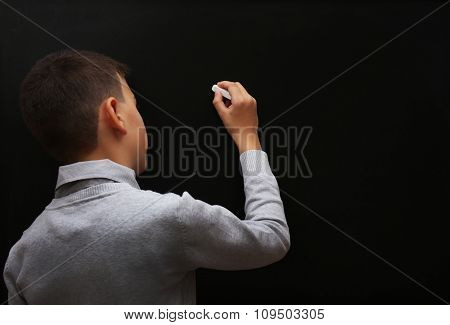 Back view of young schoolboy writing at the blackboard