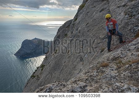 Man Climber On Edge Of Steep Mountainside In Crimea.