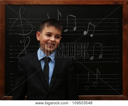 Young cute schoolboy standing at the blackboard with musical notes