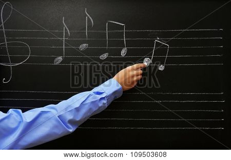 View on schoolboy's hand writing at the blackboard, close-up