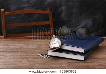 Composition of blue notebooks, eyeglasses and vintage clock on wooden table