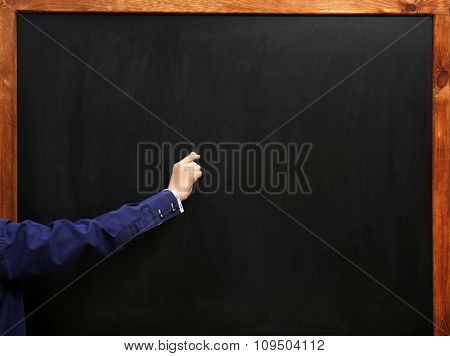 View on boy's hand writing at the clean blackboard, close-up