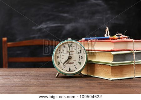 Colourful pile of books with clock on wooden table
