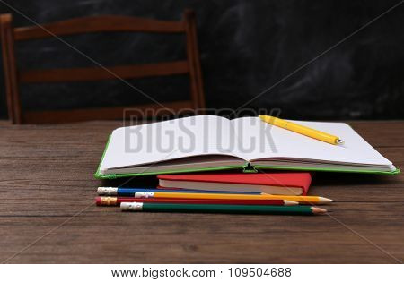 Opened book with colourful pencils on wooden table