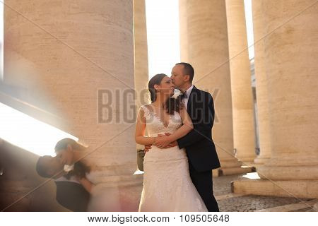 Beautiful Bridal Couple Embracing And Kissing Near Columns