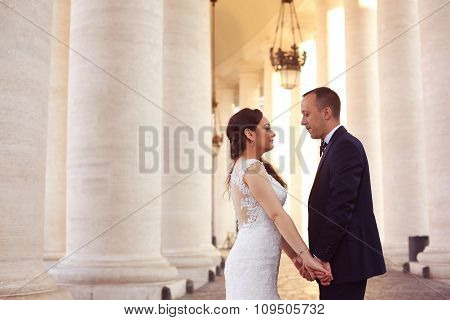 Beautiful Bridal Couple Embracing Near Columns