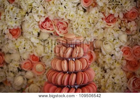 Delicious Macaroon On Stand Next To Wall Full Of Roses