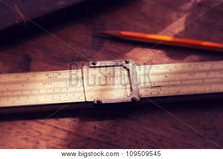 Calculation. Vintage calculating slide rule and pencil, on old desk. Intentionally shot in retro muted color. Shallow depth of field.