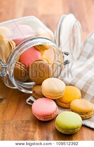 tasty colorful macarons in jar on wooden table