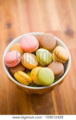 tasty colorful macarons in bowl on wooden table