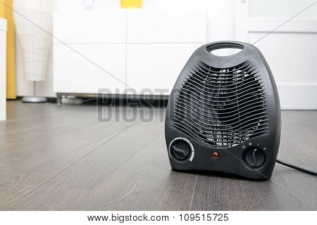 Black Electric Heater On Laminate Floor In The Room