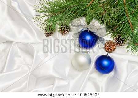 silver and blue Christmas balls with beads and pine branch on a