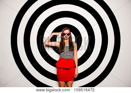 Glamorous Girl With Glasses In A Red Skirt-basque Against The Background Of Circles Gesturing