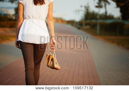 Picture Of Young Woman Hand With Shoes In The Park.