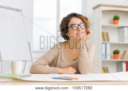 Young female stuff member sitting at the working desk.