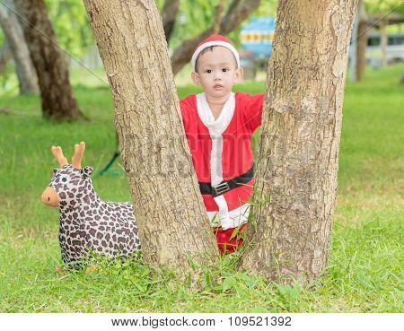 Asian baby boy in santa claus suit is playing with reindeer doll at outdoor park