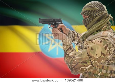 Male In Muslim Keffiyeh With Gun In Hand And National Flag On Background - Ethiopia
