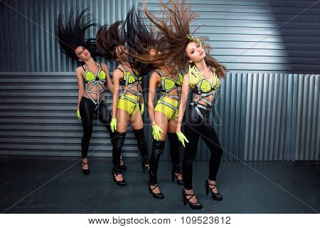 Four Confident Pretty Sexy Girls In Stage Costumes Throwing Hair