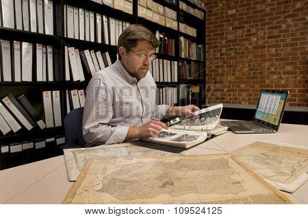 Researcher In Archive Examining Maps And Other Archival Materials