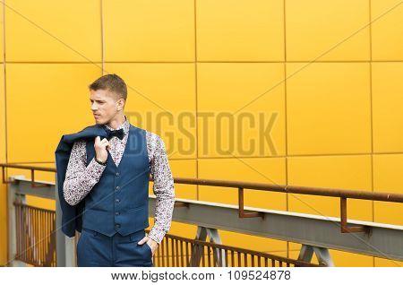 Man in blue suit standing on bridge
