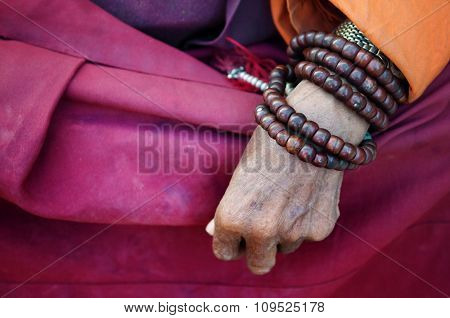 Close up old monk's hand with prayer beads.