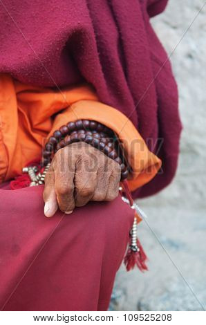 Old monk's hand with prayer beads.
