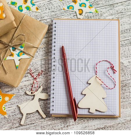 Blank Open Notepad, Christmas Gifts And Christmas Decorations On A Light Wooden Surface. Free Space