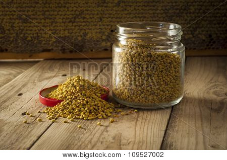 Flower pollen in glass jar and in wooden spoon