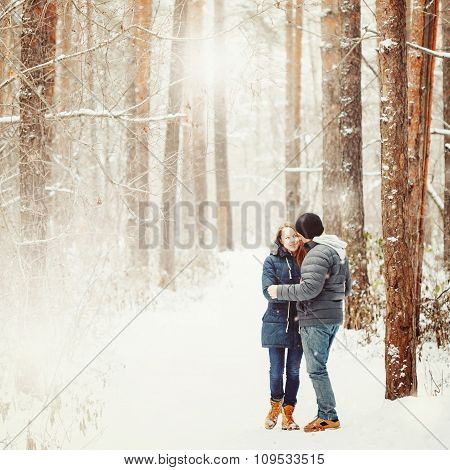 Young Couple Embracing In Winter Forest