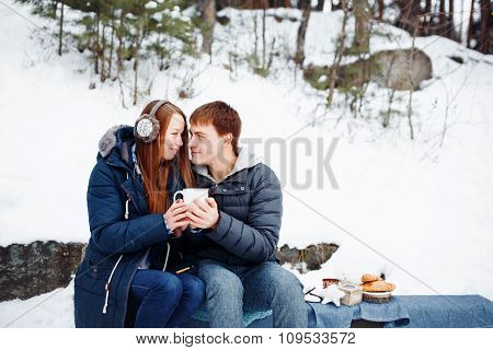 Happy Couple Sitting Outdoors In Winter