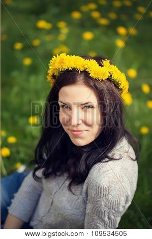 The Beautiful Girl Sits In Yellow Dandelions With A Wreath On Th
