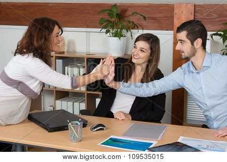 Happy Business Team With Pregnant Woman Giving High Five In Office