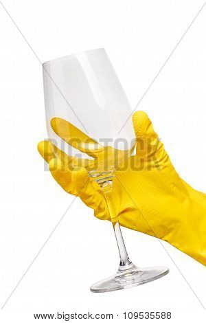 Close up of female hand in yellow protective rubber glove holding clean transparent wine glass