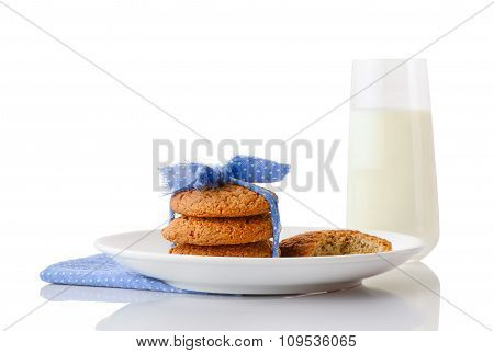 Stack of three homemade oatmeal cookies tied with blue ribbon in small white polka dots and bitten c