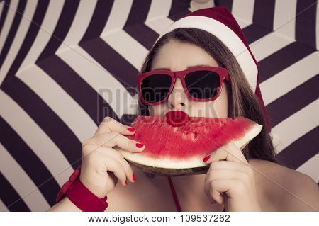 Portrait Of A Funny  Girl In Santa Claus Hat And Red Sunglasses With A Slice Of Watermelon