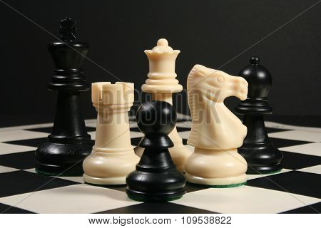 Chess pieces on board with black background